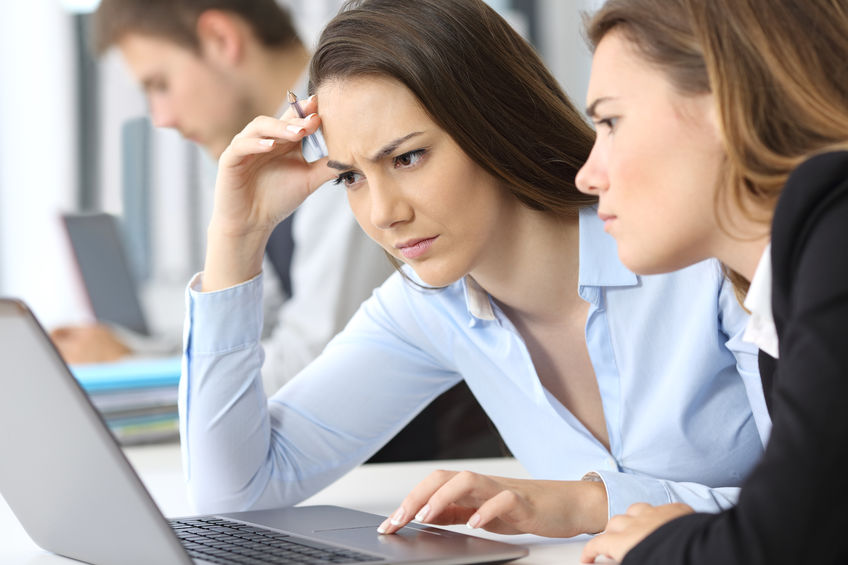 Two confused businesswomen working online with a laptop at office